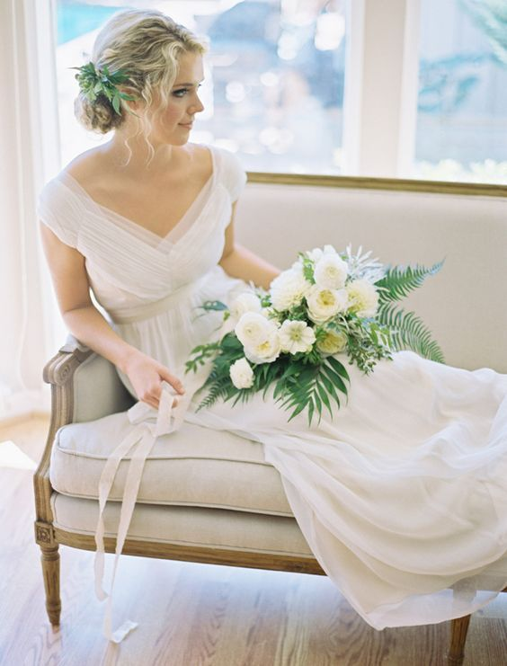 https://i.weddingomania.com/2015/03/an-airy-and-romantic-wedding-dress-with-a-deep-V-neckline-cap-sleeves-a-draped-bodice-an-empire-waist-and-a-pleated-skirt.jpg
