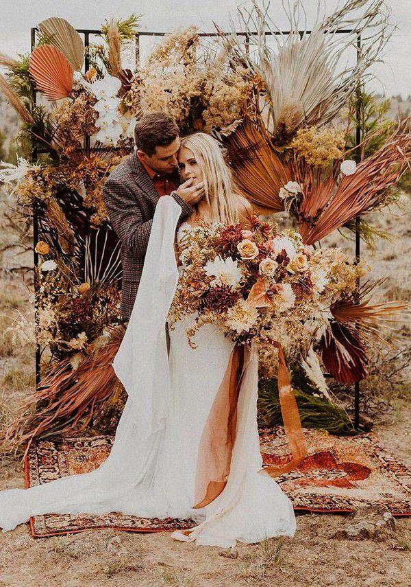 https://www.elegantweddinginvites.com/wedding-blog/wp-content/uploads/2020/08/special-rust-color-palms-and-dry-flowers-elopement-boho-wedding-arches.jpg