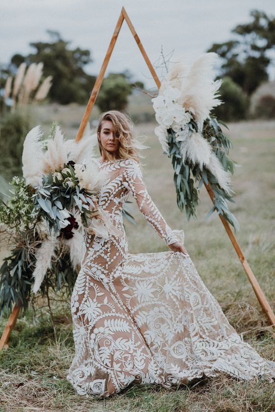 https://www.elegantweddinginvites.com/wedding-blog/wp-content/uploads/2020/03/a-boho-wooden-arch-decorated-with-greenery-fall-colored-blooms-and-pampas-grass-plus-candles-in-geometric-candle-holders.jpg