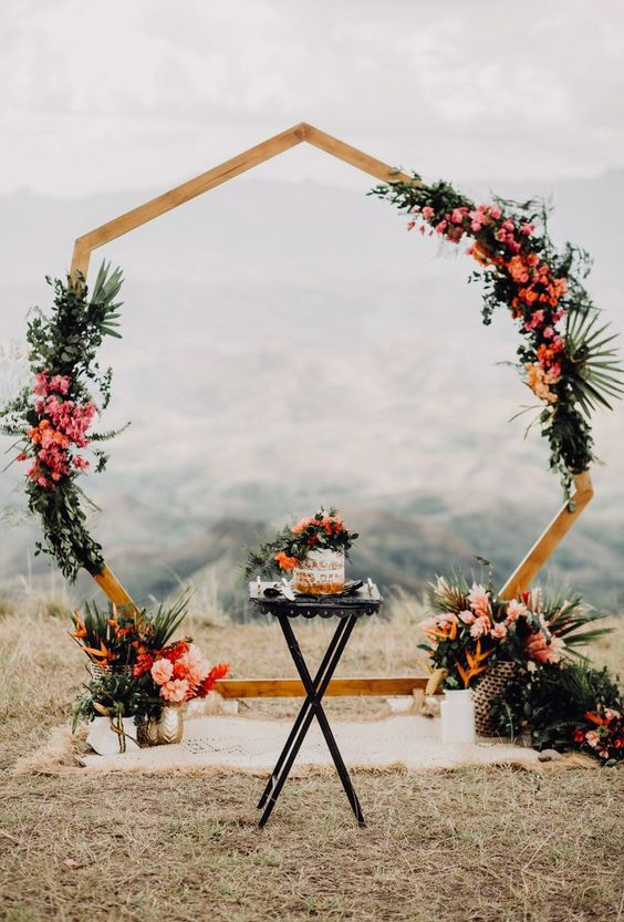 https://www.elegantweddinginvites.com/wedding-blog/wp-content/uploads/2020/03/a-polygon-wedding-arch-decorated-with-greenery-and-tropical-leaves-bright-orange-and-pink-blooms-and-tropical-fruits.jpg