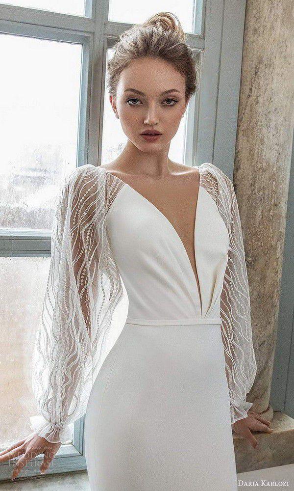 https://www.weddinginspirasi.com/wp-content/uploads/2020/07/daria-karlozi-2021-bridal-sheer-bishop-sleeves-plunging-neckline-clean-minimalist-sheath-wedding-dress-chapel-train-4-zv.jpg