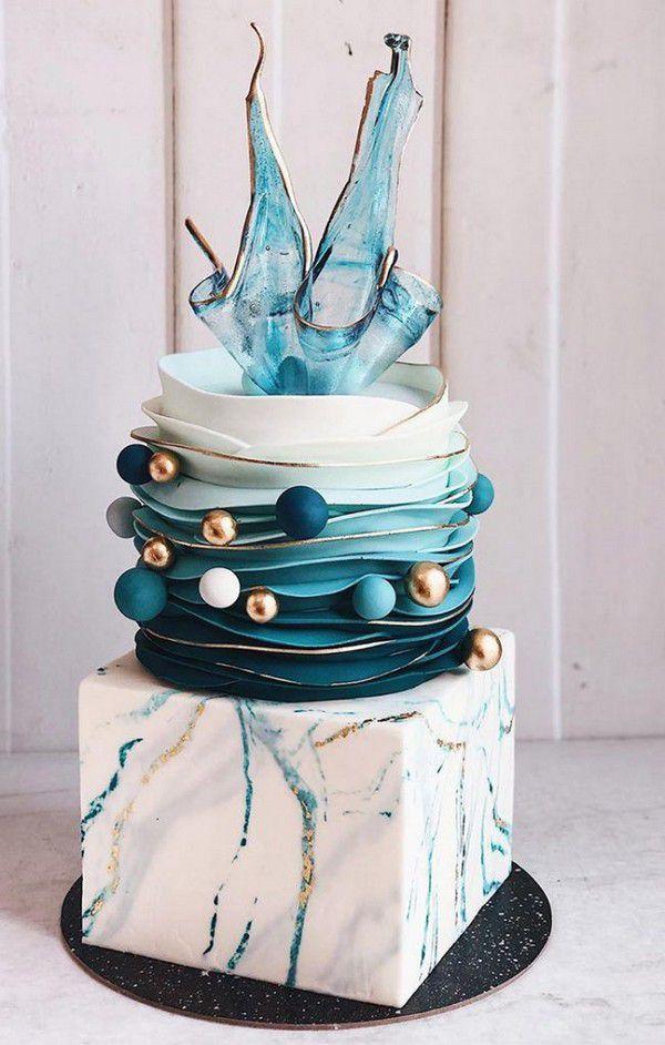 https://www.elegantweddinginvites.com/wedding-blog/wp-content/uploads/2020/09/teal-blue-gold-ball-modern-wedding-cake-with-unique-isomalt-cake-topper-652x1024.jpg