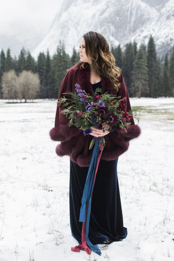 https://i.weddingomania.com/2018/12/08-a-statement-plum-colored-capelet-with-fur-over-a-navy-wedding-dress-is-a-gorgeous-and-bold-idea.jpg