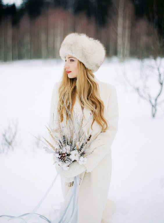 https://i.weddingomania.com/2018/12/23-a-fur-hat-and-a-white-logn-cardigan-will-keep-you-warm-and-comfortable-even-outside.jpg